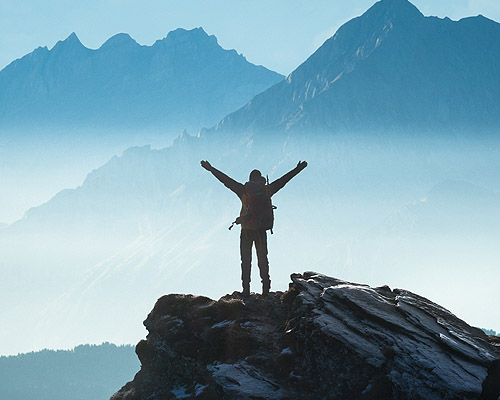 Man on top of mountain raising hands