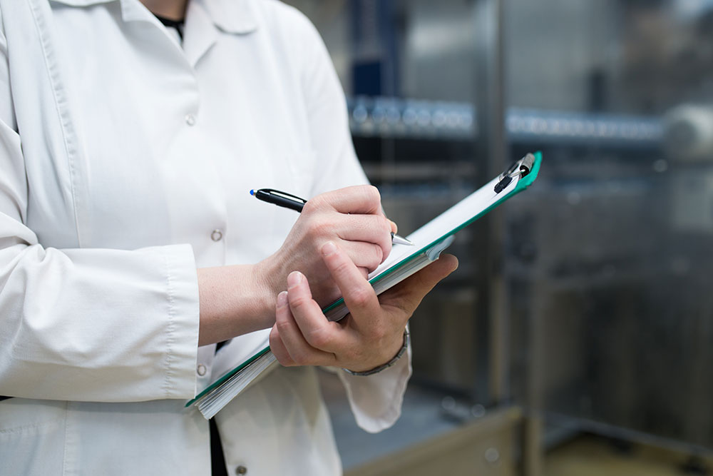 Image of medical professional writing on a clipboard