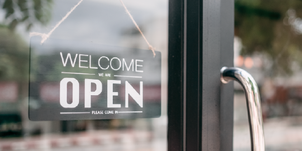 "A sign in a shop window reads ""Welcome, we're open."""