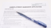 An unemployment insurance application form with a pen