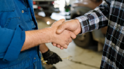 Two coworkers shake hands in a workshop