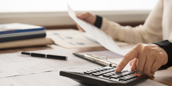 A financial advisor uses a calculator while reviewing financial documents.