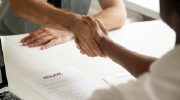 An employer shakes the hand of a new hire.