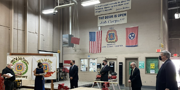 Secretary Walsh and others stand in a Tennessee Job Corps Center. A sign on the wall reads: I don't want nobody to give me nothing. Open up the door and I'll get it myself. James Brown. Another reads: The Door Is Open: Job Corps!