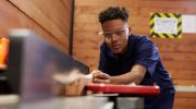 A young man cuts a piece of wood using carpentry tools.