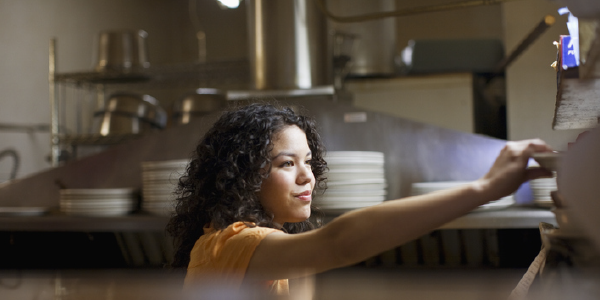 A woman working in a kitchen reaches for a food order.