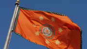 The flag of the Cherokee nation waves in a breeze.