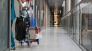A custodian moves cleaning materials through a corridor.