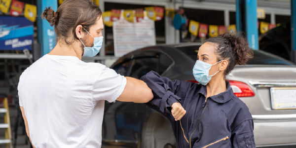 Two mechanics, a man and a woman, bump elbows at work.