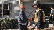 Two men shake hands outside a storm-damaged house. One wears an OSHA protective vest, as well as gloves and hard hat.