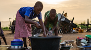 Two young girls in Togo wash dishes outside their home. Photo credit: Jordan Rowland, Unsplash.