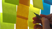 Close-up shot of Post-It notes covering a board. A woman writes on a yellow note with a pen.
