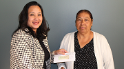 Garment worker Bertha Gonzalez (right) receives a check for back wages from Wage and Hour Division Los Angeles District Director Kimchi Bui.