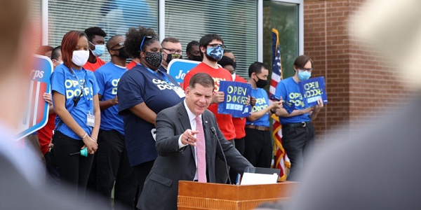 Secretary Walsh speaks at a podium. Behind him stand Job Corps students wearing shirts that say 'Open Doors.'