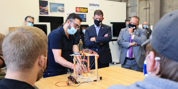 Secretary Walsh observes college students showing a tool they've engineered.