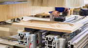 Close-up shot of a woodworking machine cutting a detailed design into a cabinet door.