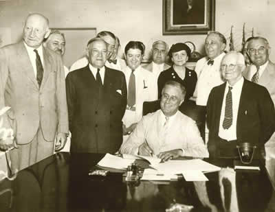 Secretary Frances Perkins standing directly behind President Franklin D. Roosevelt during the signing ceremony for the Social Security Act (1935).