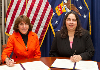 Beth Marks, NOND President, and ODEP Assistant Secretary Kathy Martinez, sign the Alliance agreement.