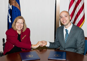Jennifer Sheehy, ODEP Deputy Assistant Secretary, and Kenneth Matos, Senior Director of Research, Families and Work Institute, shake hands over the signed Allliance agreement.