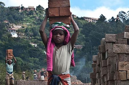 Child carrying bricks